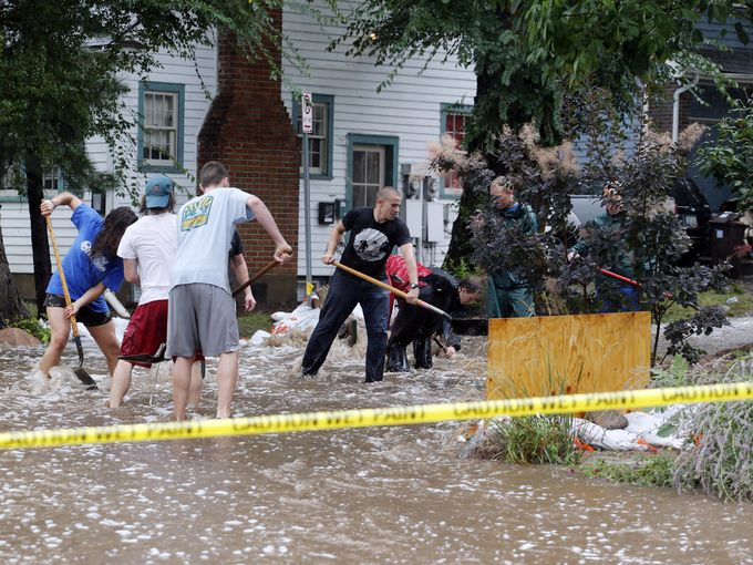 Residents of an apartment building work to divert floodwater from their homes in Boulder, Colo.. Flash flooding in Colorado has cut off access to towns, closed the University of Colorado in Boulder and left at least three people dead.  Ed Andrieski, AP