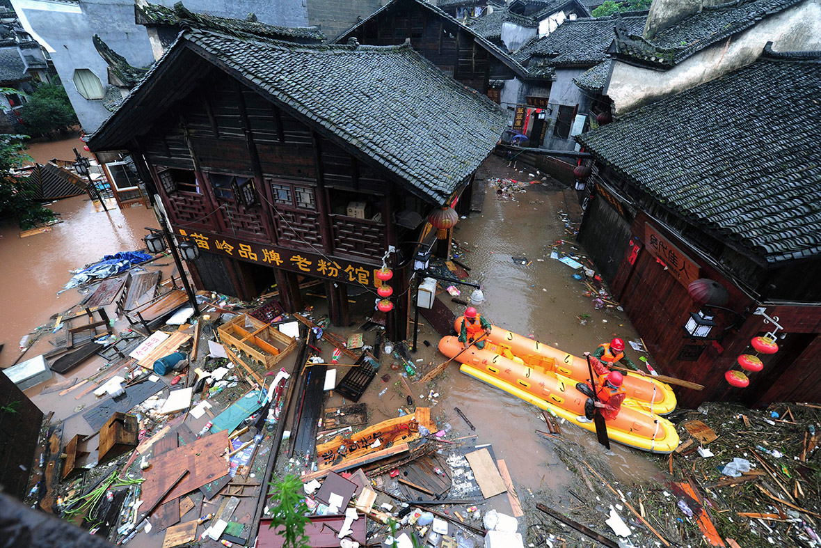 Workers clean up debris from a flooded street in the ancient town of Fenghuang. Reuters