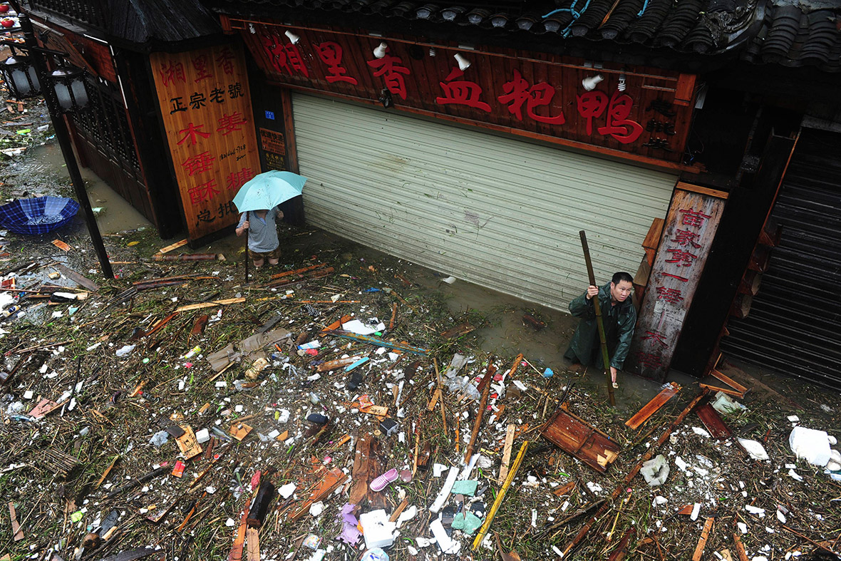 People clear debris on a flooded street in Fenghuang. Reuters