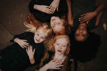 graceful diverse girls lying together on ground
