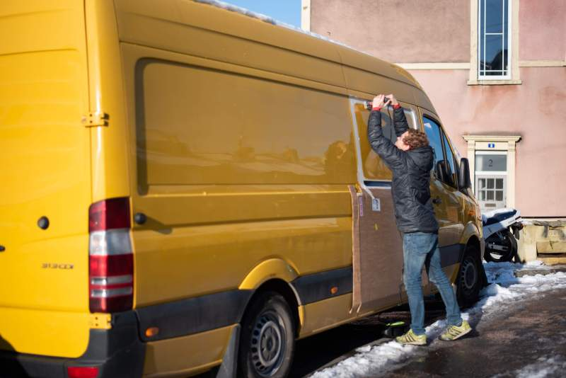 man cutting a hole in the side of a Sprinter van conversion with a Jigsaw in order to install windows