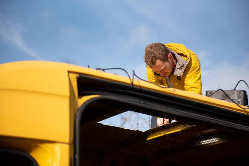 man cutting a hole in a yellow Sprinter van conversion campervan to install a skylight
