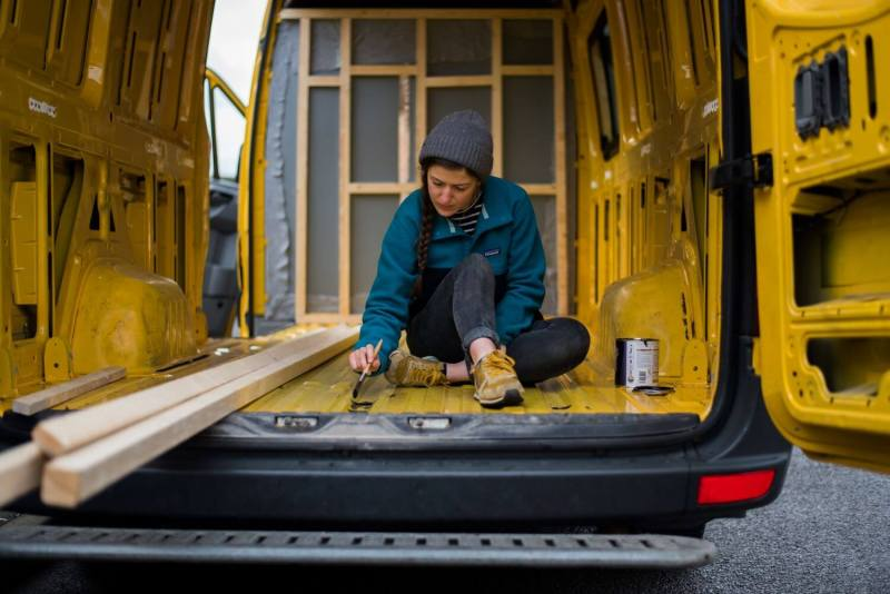 How to insulate your van conversion - girl painting hammerite onto rust on a Mercedes Sprinter camper van