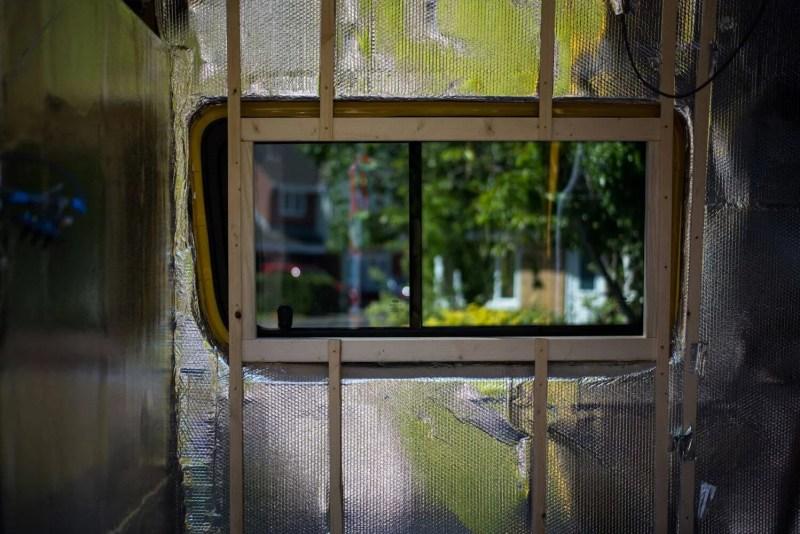 Wooden window frame in a Mercedes Sprinter van conversion