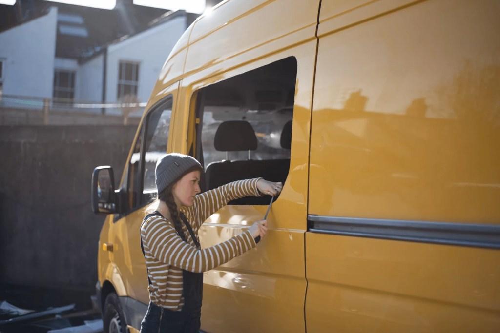 girl filing a window installing windows in a campervan