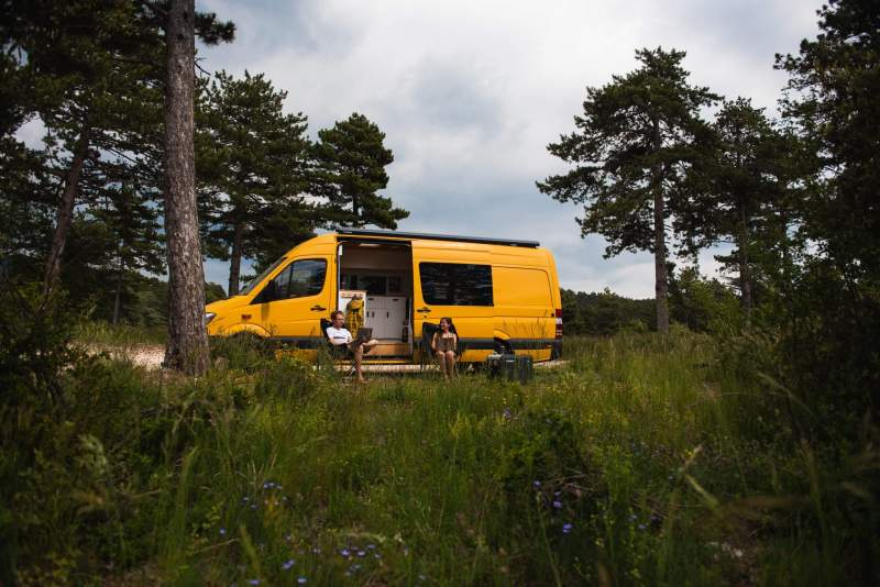 how to become a digital nomad man and woman doing online work remote work outside a campervan in the wilderness forest