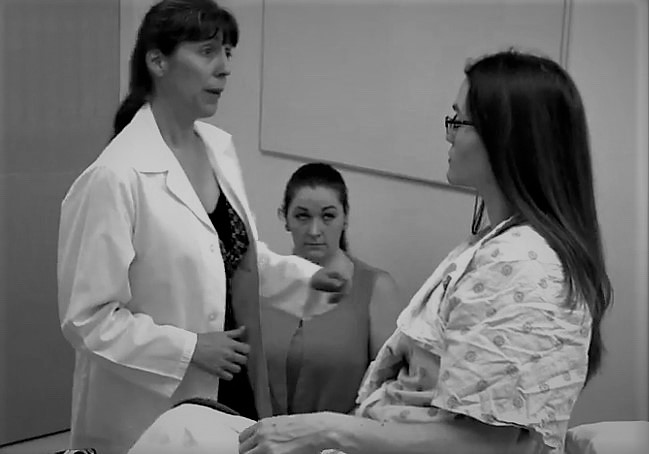 Gynecologic Teaching Associate providing instruction to female learner