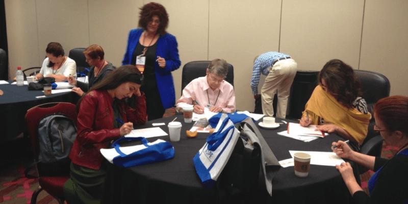 Workshop participants completing worksheets at tables