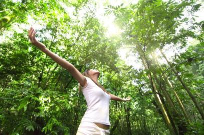 imagen mujer en bosque brazos abiertos