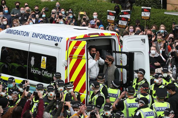One of two men are released from the back of an Immigration Enforcement van accompanied by Mohammad Asif, director of the Afghan Human Rights Foundation, in Kenmure Street, Glasgow which is surrounded by protesters. (Image: Andrew Milligan/PA Wire)