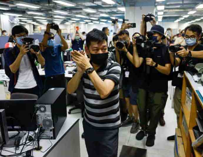 Lam Man-chung, executive editor-in-chief of Apple Daily, applauds colleagues on the paper's last day. Photograph: Lam Yik/Reuters