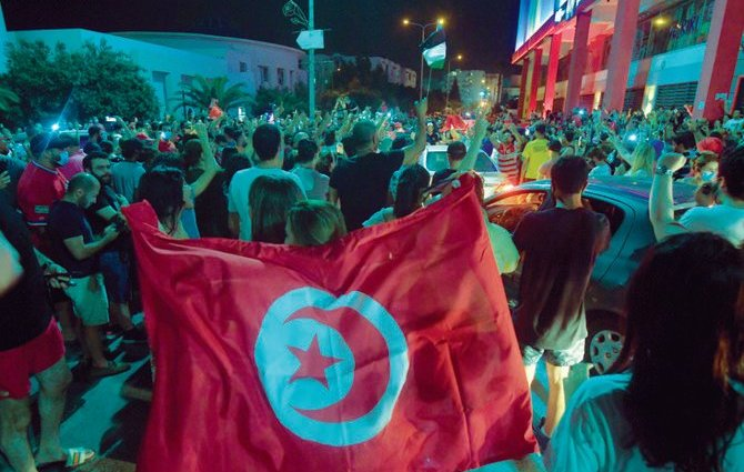 Tunisians celebrated on July 25 after President Kais Saied announced the dismissal of the country's prime minister following nationwide protests. (AFP)
