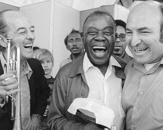 George Wein, right, with the trumpeter Bobby Hackett and Louis Armstrong at the Newport Jazz Festival in 1970. The festival, which Mr. Wein first presented in 1954, became a model for how to present music in the open air on a grand scale.Credit...J Walter Green/Associated Press