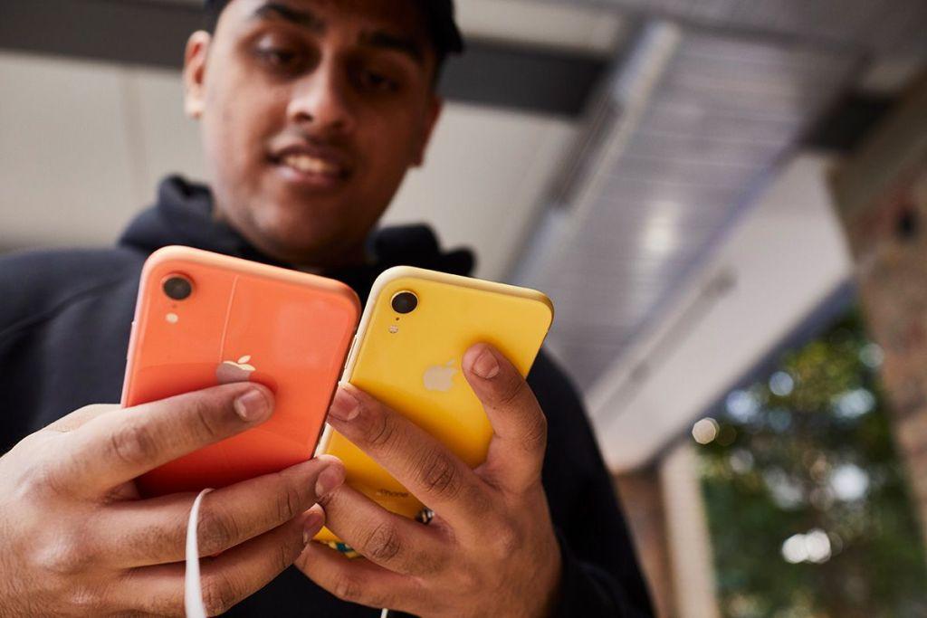 Un hombre sujeta dos iPhone XR en una Apple Store