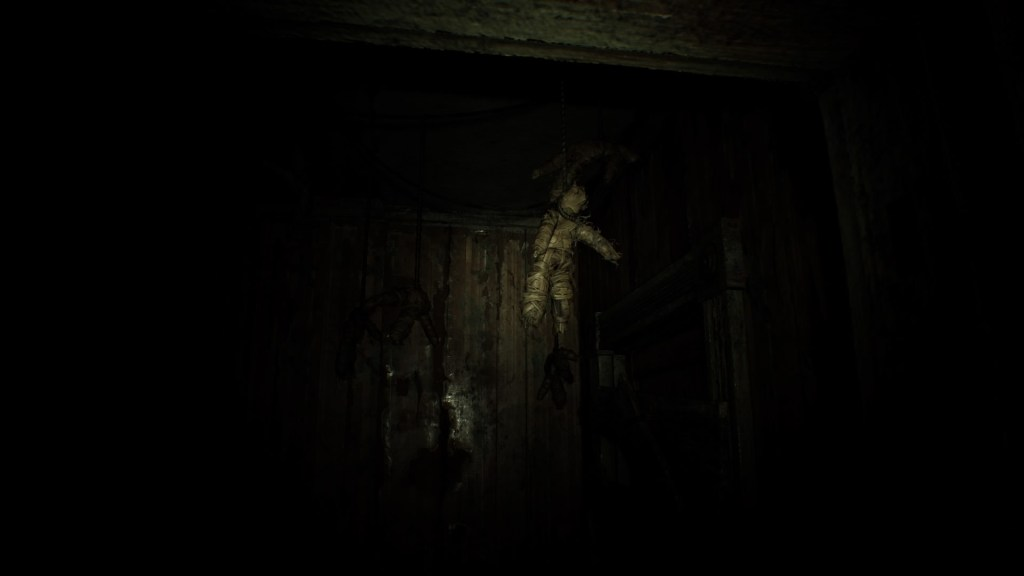 A tattered doll hangs from a door frame in beginning hour