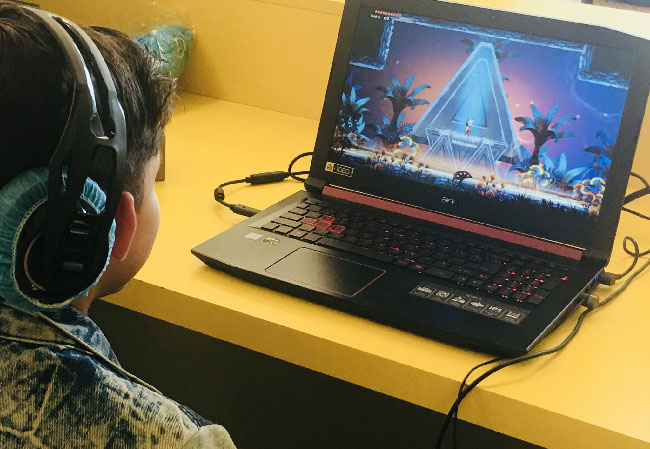 """One person playing a demo of """"Balam and the Spirit Within"""" on a computer with headphones, in the yellow rooms of the Santa Monica College Center for Media and Design."""