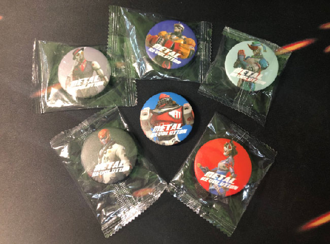 "Six badges wrapped in plastic, each with a different character from ""Metal Revolution."""