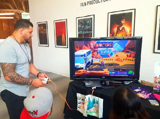 "A person plays ""The Last Friend"" demo on a big television at a booth in the Santa Monica College Center for Media and Design."