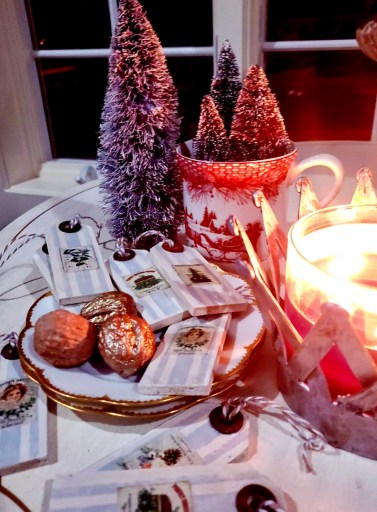 Christmas gift tags with candles lit and bottle brush trees in the evening