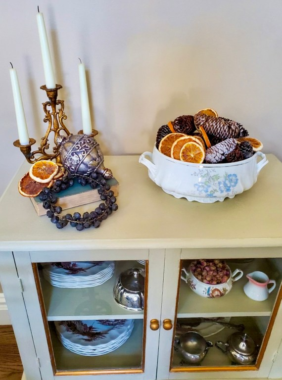 A bowl holding dried orange slices and pine cones.