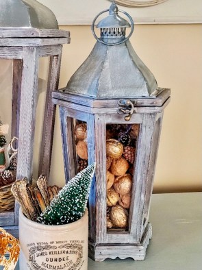 small lantern filled with walnuts.  White crock filled with silver and a small bottle brush tree