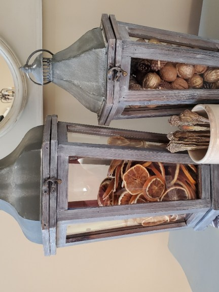 Two lanterns filled with orange slices, nuts and pinecones.  A white dish filled with silverware