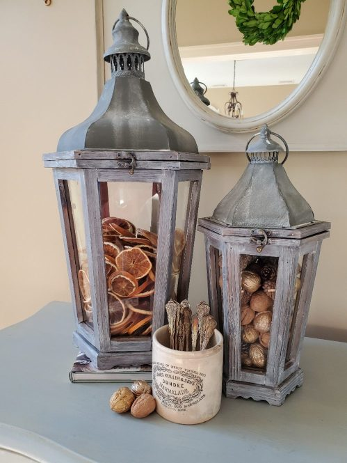 The large lantern filled with dried orange slices.  The small lantern filled with gold, natural walnuts and pinecones.  A white jar is filled weith silver