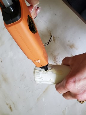 adding hot glue to the base to resemble real wax drips on the décor DIY