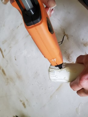 adding more hot glue to look like wax drips on the rustic Christmas décor DIY