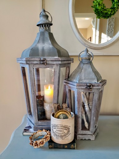 Large lantern holds a battery operated candle inside a flower pot with books near the pot.  Smaller lantern filled with spindles.   White crock filled with silver and a small picture.  A crown is leaning