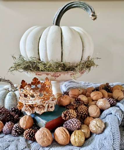 A pumpkin in a dish with walnuts and pinecones.  Crowns on books