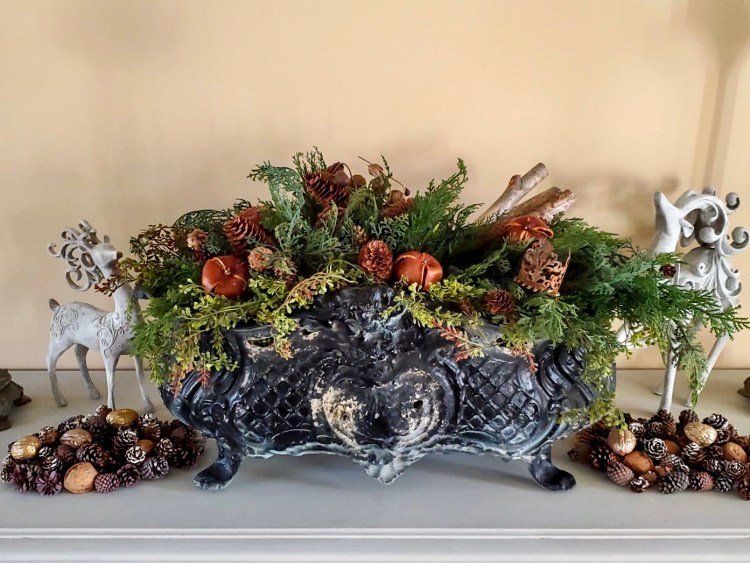 Jardieneire filled with greens, pinecones, a small crown and birch logs with clementine.  Deer are on either side with pinecones and walnuts