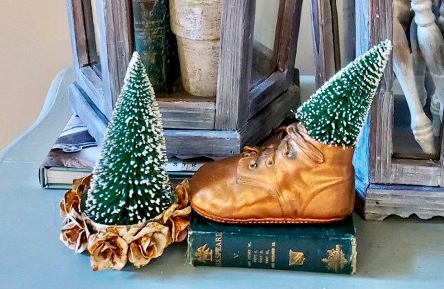 Close up of a baby shoe filled with a bottle brush tree.  A rose crown holds a medium bottle brush tree