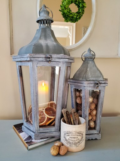 Large lantern filled with dried orange slices and battery  operated candle.  Small lantern filled wiyh walnuts and pinecones.  White jar filled with silver