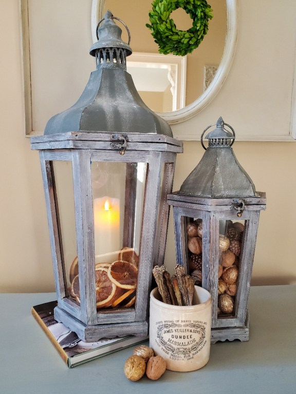 Large lantern filled with orange slices surrounding a battery operated candle.  Smaller lantern filled with walnuts and pinecones. White crock filled with silver walnuts are next to the crock