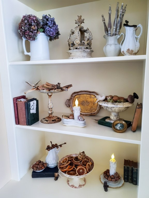 fall decor on the bookcase.  showing the candles lit  doorknobs, old books and fall decor