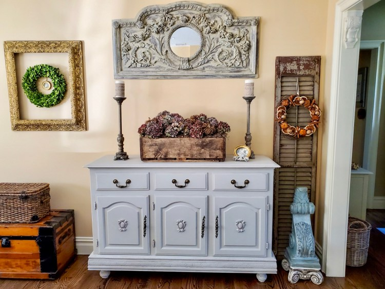 picture of natrual fall decor on the buffet in the great room.  Dry hydrangeas fill a wooden crate with a basket and old steamer trunk next to it.  An old shutter with a corbel on a pedestal  under the corbel  a wreath hangs on the shutter  a large mirror hangs over the buffet