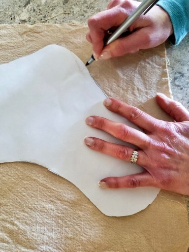 tracing the outline of the stocking on fabric
