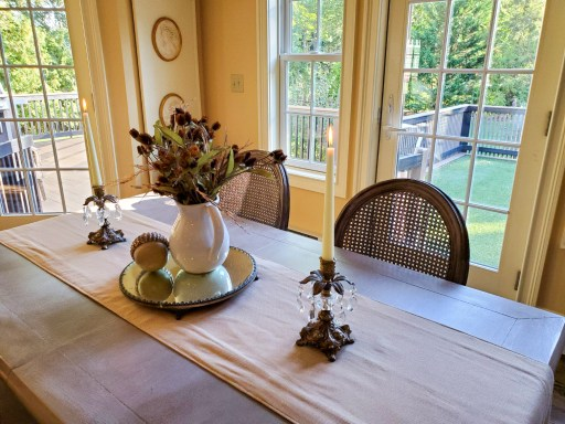 Table with candles lit with a centerpiece of a pitcher, a mirror and an acorn for fall decor  Candles are lit on the table
