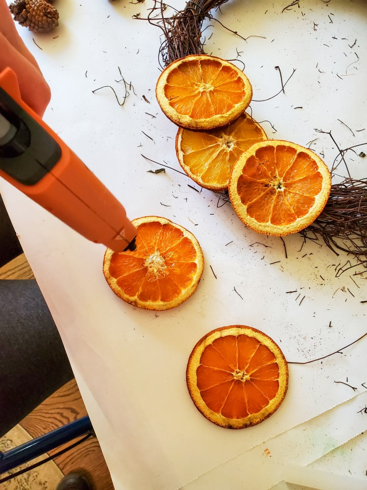 showing a few orange pieces glued to the wreath.  Also I am adding glue to another orange for the dried citrus wreath