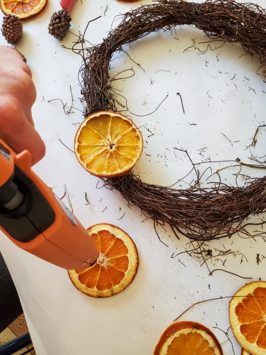 showing how I use the hot glue gun to add a piece of orange to my wreath