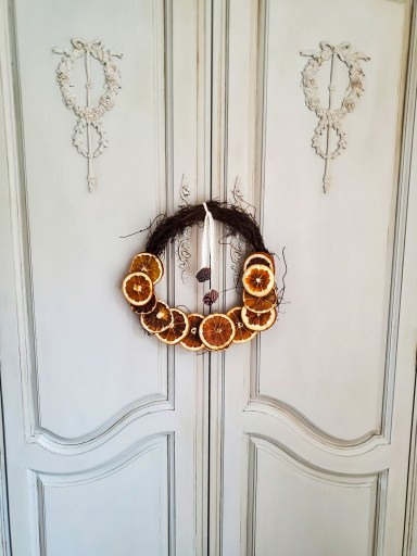 a close up of the dried citrus wreath with ribbon tied around and small pinecones hanging from the ribbon
