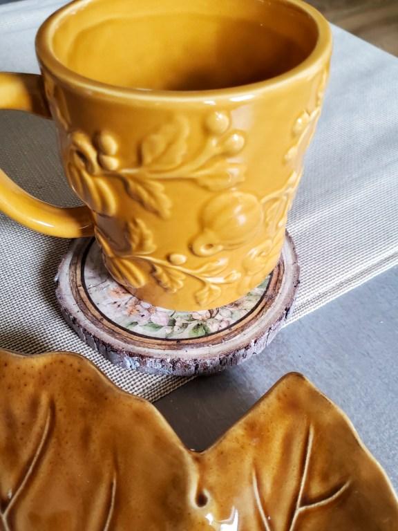a mug with pumpkins on it sitting on the wood coaster