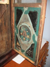 The inside of the door. A mouse lived in the clock for a while, note the door below the painted glass.