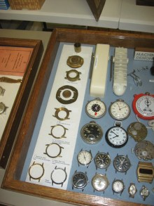 How a watch case was made is shown in the left of the display. Don Sprayer explained how the brand rod at the top is hot forged into the rough case, cut out and finished. Diamond turning gives a polished surface, then the case is nickel plated if desired.