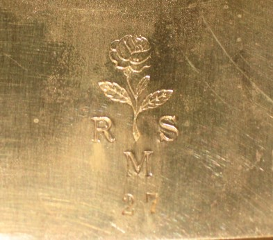 Logo on back plate R M S 27 and flower drawing