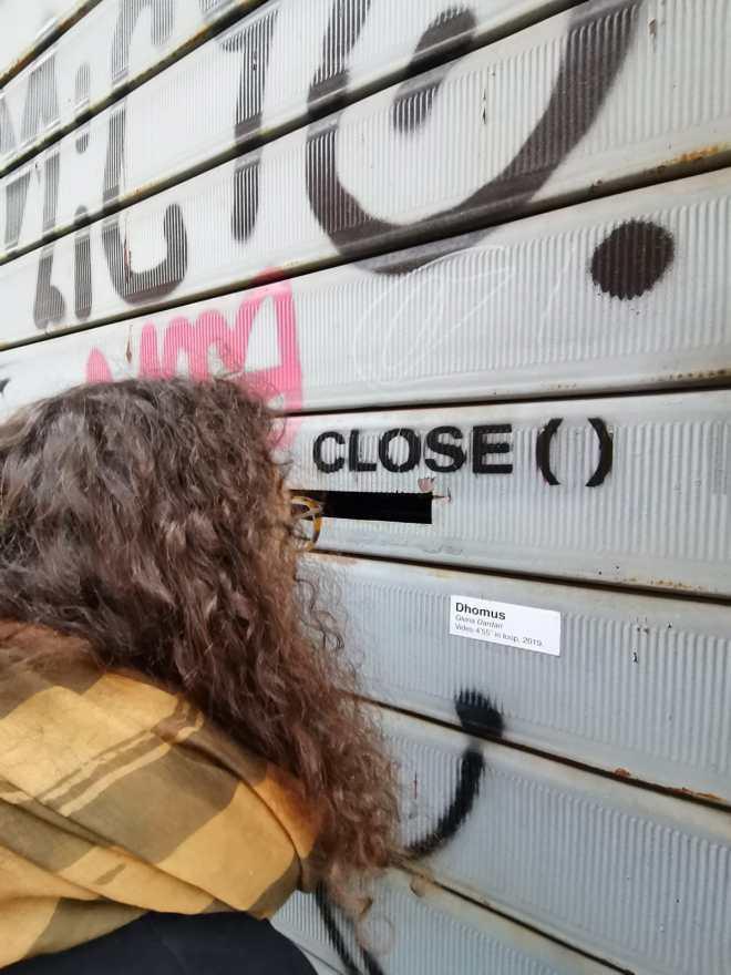 Fruizione della video istallazione Dhomus attraverso la serranda di Parsec © Alessandro Casagrande