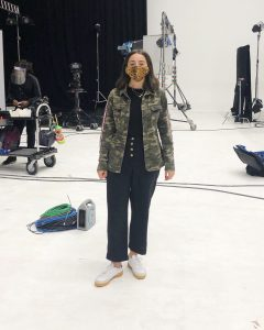 Woman in camo print khaki jacket on a TV set