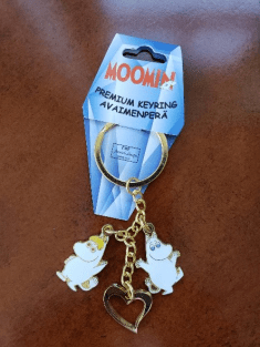 Image of a Moomin keychain sitting on a hotel desk.