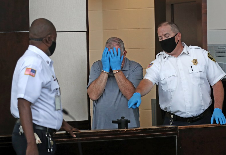 Patrick M. Rose Sr. covered his face during his arraignment in West Roxbury District Court on multiple charges of indecent assault on a child under 14.